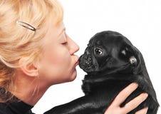 Leuke blonde die een zwart pug puppy kust stock foto