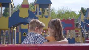 Leuke blonde jongen het kussen wang van een mooie meisjeszitting op de bank voor de speelplaats Een paar gelukkig stock video
