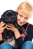 Leuke blonde met een pug puppy stock afbeeldingen