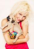 Leuke blonde met een pug puppy royalty-vrije stock fotografie