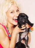 Leuke blonde met een pug puppy stock afbeelding
