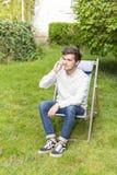 Leuke blonde tiener op de telefoonzitting in de tuin Royalty-vrije Stock Afbeeldingen