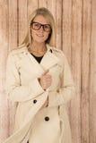Leuke blonde vrouw die glazen dragen en witte laag gesloten houden Royalty-vrije Stock Afbeelding