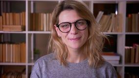 Leuke blondeleraar die op middelbare leeftijd in glazen gelukkig in camera glimlachen die blij bij de bibliotheek zijn stock video