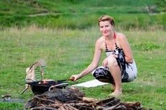 Leuke blondemeisje gebakken barbecue in uitje in aard Royalty-vrije Stock Afbeelding