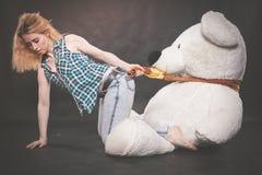 Leuke blondetiener in jeans en de spelen van het plaidoverhemd met haar reusachtige ijsbeer van Teddy in gele sjaal op zwarte ach stock foto