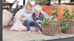 Leuke broer en weinig zuster die op een mooie veranda in de zomer koesteren stock videobeelden