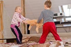 Leuke broer en zuster die een touwtrekwedstrijd hebben Stock Afbeeldingen