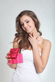 Leuke brunette die een gift openvouwt Royalty-vrije Stock Afbeelding