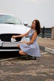 Leuke brunette en luxeauto Stock Afbeeldingen