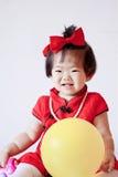 Leuke Chinees weinig baby in de rode gele ballon van het cheongsamspel Stock Fotografie