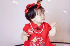 Leuke Chinees weinig baby in de rode zeepbels van het cheongsamspel Stock Fotografie