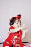Leuke Chinees weinig baby in de rode zeepbels van het cheongsamspel Stock Foto's