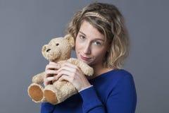 Leuke dame die haar het snoezige stuk speelgoed herinneren steunen zich Stock Foto's