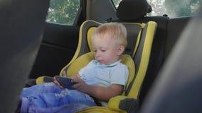 Leuke de jongenszitting van de peuterbaby in autozetel en het letten van een op video van smartphone Jong geitje het spelen in de stock video