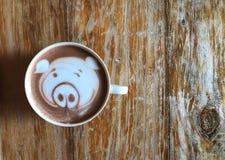 Leuke de kunstkoffie van het varkensgezicht latte in witte kop op houten lijst stock foto's