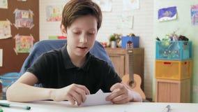 Leuke de origamiboot en spelen van jongensvouwen met het stock videobeelden