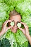 Leuke die vrouw met saladebladeren rond haar hoofd met cucum worden geschikt Stock Fotografie
