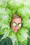 Leuke die vrouw met saladebladeren rond haar hoofd met cucum worden geschikt Royalty-vrije Stock Foto's