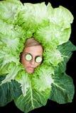 Leuke die vrouw met saladebladeren rond haar hoofd met cucum worden geschikt Stock Foto's