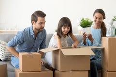 Leuke dochter die mammapapa helpen dozen in nieuw huis uitpakken stock foto's