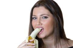 Leuke donkerbruine dame, die een gepelde banaan eten Royalty-vrije Stock Foto