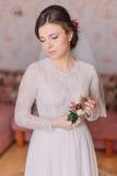 Leuke droevige bruid thuis in witte huwelijkskleding, voorbereidingenconcept Portret van offerte gedeprimeerd meisje in toga royalty-vrije stock foto's
