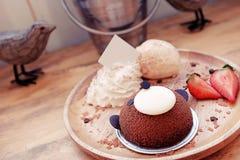 Leuke en heerlijke die bruin draagt cake met aardbei, vanilleroomijs en slagroom in houten plaat wordt gediend Royalty-vrije Stock Foto