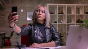 Leuke enthousiaste Kaukasische blondevrouw in het nemen selfies op haar telefoon terwijl het zitten bij Desktop terwijl binnen zi stock video