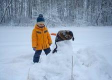 Leuke Europese jongen en sneeuwman in het hout stock afbeeldingen