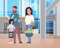 Leuke Familie bij Gelukkige Pasen-Vakantieouders die met de Bloemen van de Jong geitjeholding thuis vieren Royalty-vrije Stock Foto's