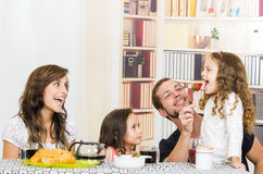 Leuke familie met twee meisjes die ontbijt eten Stock Foto