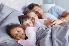 Leuke familieslaap in bed Stock Foto's