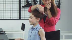 Leuke gelukkig weinig haar die haar haar krijgen dat door een kapper bij de schoonheidssalon wordt gedaan stock video