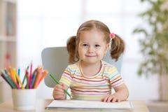 Leuke gelukkig weinig tekening van het kindmeisje met potloden in opvangcentrum royalty-vrije stock fotografie