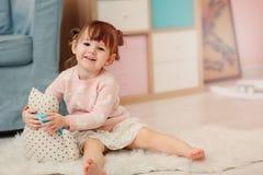 Leuke gelukkige 2 jaar het oude babymeisje spelen met speelgoed thuis Royalty-vrije Stock Foto