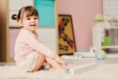 Leuke gelukkige 2 jaar het oude babymeisje spelen met speelgoed thuis Stock Foto's