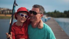 Leuke gelukkige jonge jongen met zijn vader bij een meer stock fotografie