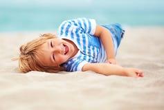 Leuke gelukkige lachende jongen, jong geitje die pret op zandig strand hebben, de zomervakantie Stock Afbeelding