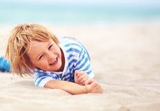 Leuke gelukkige lachende jongen, jong geitje die pret op zandig strand hebben, de zomervakantie Royalty-vrije Stock Foto