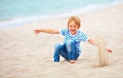 Leuke gelukkige lachende jongen, jong geitje die pret op zandig strand hebben, de zomervakantie Stock Fotografie