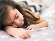 Leuke gelukkige meisjeslaap en binnen dromend en bed die haar stuk speelgoed koesteren Royalty-vrije Stock Afbeeldingen