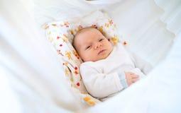 Leuke gelukkige pasgeboren baby die op bed liggen royalty-vrije stock foto's