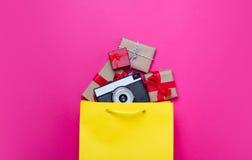 Leuke giften en koele camera in het winkelen zak en koele laptop op wo Stock Foto's