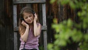 Leuke girlie geniet van muziek met hoofdtelefoons bij het zitten in de binnenplaats van een dorp stock video