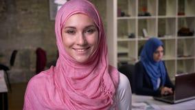 Leuke glimlach van moslimwijfje in roze hijab die, bureau het werk stemming, baksteenstudio binnen, het Midden-Oosten vibes bevin stock videobeelden