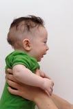 Leuke glimlachende baby die door zijn mening van het moederprofiel wordt gehouden stock afbeeldingen