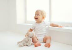 Leuke glimlachende baby met teddybeerstuk speelgoed zitting thuis Stock Fotografie