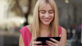 Leuke glimlachende dame die modieuze digitale tablet op de straat gebruiken stock videobeelden