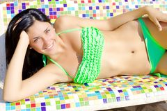 Leuke glimlachende jonge vrouw in bikini op het kleurrijke schot van de bankgulden middenweg royalty-vrije stock fotografie